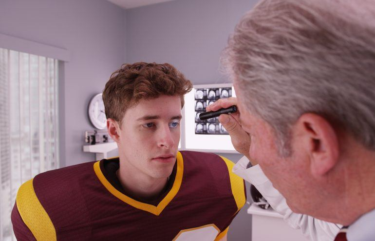 Sports chiropractor evaluating a TBI patient