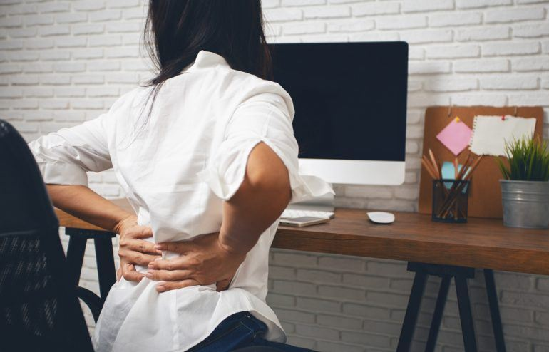 Business woman suffering from back pain and poor posture at her work-from-home set up.